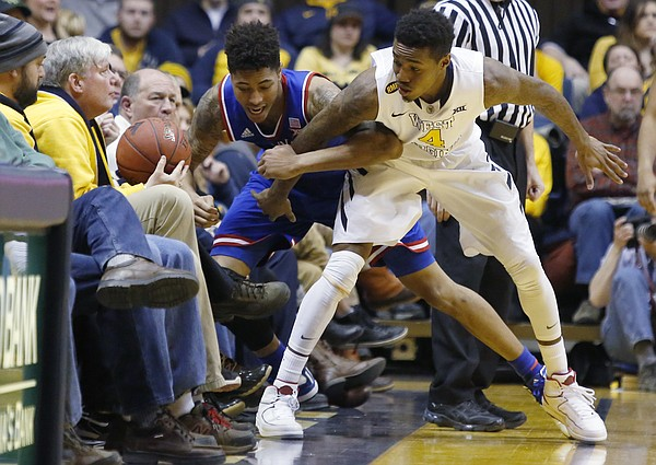 Kansas guard Kelly Oubre, Jr. (12) goes out of bound battling for a ball with West Virginia guard Daxter Miles Jr. (4) during the Jayhawks 62-61 loss game against the West Virginia Mountaineers Monday, February 16, 2105  in Morgantown, W.V.