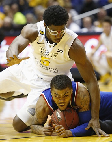 Kansas guard Frank Mason III and West Virginia forward Devin Williams (5) struggle for a loose ball Monday, February 16, 2105  in Morgantown, W.V.