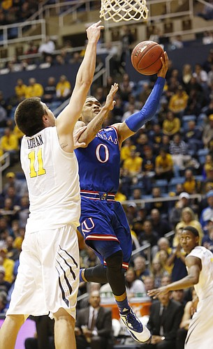 Kansas guard Frank Mason III (0) drives past West Virginia forward Nathan Adrian (11) to give the Jayhawks a late 61-60 lead against the Mountaineers Monday, February 16, 2105  in Morgantown, W.V. West Virginia scored the final basket to defeat KU 62-61.