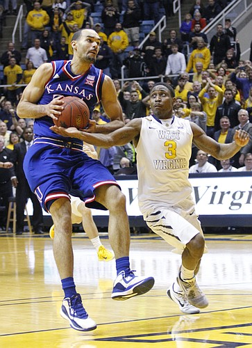 Kansas forward Perry Ellis (34) is defended by West Virginia guard Juwan Staten (3) after Ellis caught a long pass from Jamari Traylor in an attempt for a last-second shot at the end of the Jayhawks 62-61 loss game against the West Virginia Mountaineers Monday, February 16, 2105  in Morgantown, W.V.