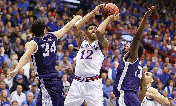 Kansas guard Kelly Oubre Jr. (12) hangs for a shot between TCU forward Kenrich Williams (34) and forward Chris Washburn during the second half, Saturday, Feb. 21, 2015 at Allen Fieldhouse.