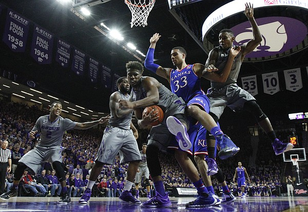 Kansas State forward Nino Williams (11) pulls a rebound away from Kansas forward Landen Lucas (33) during the second half, Monday, Feb. 23, 2015 at Bramlage Coliseum. At right is Kansas State guard Nigel Johnson (23).