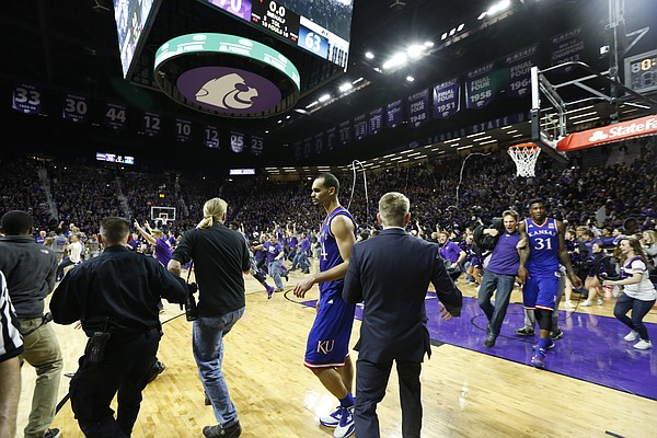 In this sequence of images a court-rusher checks Kansas forward Jamari Traylor on his way toward the Kansas players before being temporarily stopped by security.