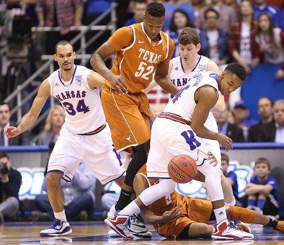 Kansas guard Devonte Graham looks for a loose ball with Texas forward Myles Turner (52) and teammate Perry Ellis during the first half on Saturday, Feb. 28, 2015 at Allen Fieldhouse.