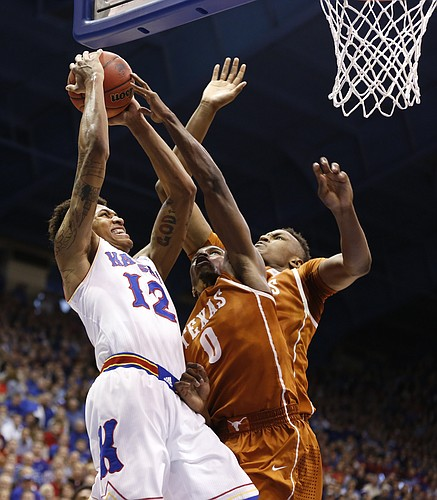 Kansas guard Kelly Oubre Jr. (12) goes hard to the bucket against Texas guard Kendal Yancy (0) and forward Myles Turner during the second half on Saturday, Feb. 28, 2015 at Allen Fieldhouse.