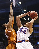 Kansas forward Perry Ellis hangs for a shot over Texas forward Jonathan Holmes during the second half on Saturday, Feb. 28, 2015 at Allen Fieldhouse.