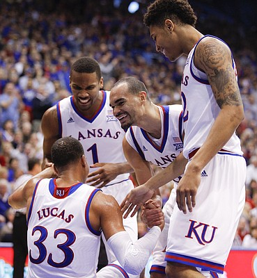 Kansas guard Wayne Selden Jr. (1), forward Perry Ellis, center, and guard Kelly Oubre Jr. celebrate with Kansas forward Landen Lucas (33) after Lucas took a charge from Baylor forward Rico Gathers (2) during the second half, Saturday, Feb. 14, 2015 at Allen Fieldhouse.