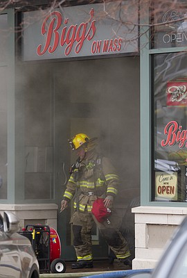 A Lawrence fireman comes out of a smoke-filled Biggs on Mass, 719 Massachusetts St., around 1 p.m. Tuesday, March 3, 2015.