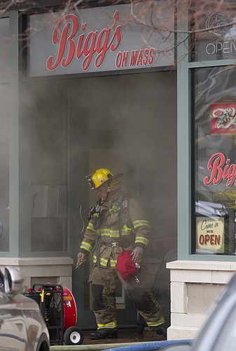 A Lawrence fireman comes out of a smoke-filled Biggs on Mass, 719 Massachusetts St., around 1 p.m. Tuesday, as crews worked to control a fire.