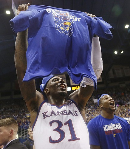 Kansas forward Jamari Traylor (31) hoists a Big 12 championship t-shirt after the Jayhawks defeated the West Virginia Mountaineers Tuesday, March 4, 2015 at Allen Fieldhouse.