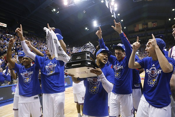 Kansas guard Frank Mason III (0), center, holds the 2015 Big 12 trophy after KU defeated the West Virginia Mountaineers 76-69 Tuesday, March 4, 2015 at Allen Fieldhouse..