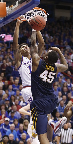 Kansas guard Kelly Oubre, Jr. (12) puts down a dunk in the first half of the Jayhawks game against the West Virginia Mountaineers Tuesday, March 4, 2015 at Allen Fieldhouse.