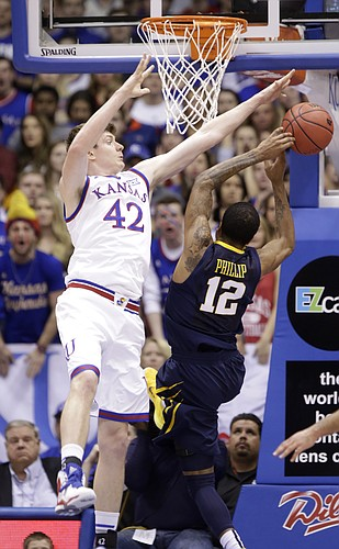 Kansas center Hunter Mickelson (42) goes for a block against West Virginia guard Tarik Phillip (12) during the Jayhawks game against the West Virginia Mountaineers Tuesday, March 4, 2015 at Allen Fieldhouse..