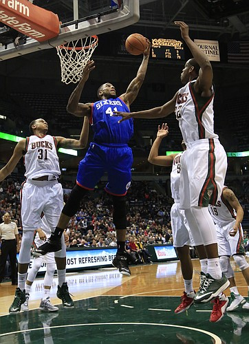 Philadelphia 76ers forward Thomas Robinson, center, grabs a rebound against the Milwaukee Bucks during the first half of an NBA basketball game Wednesday, Feb. 25, 2015, in Milwaukee. (AP Photo/Darren Hauck)