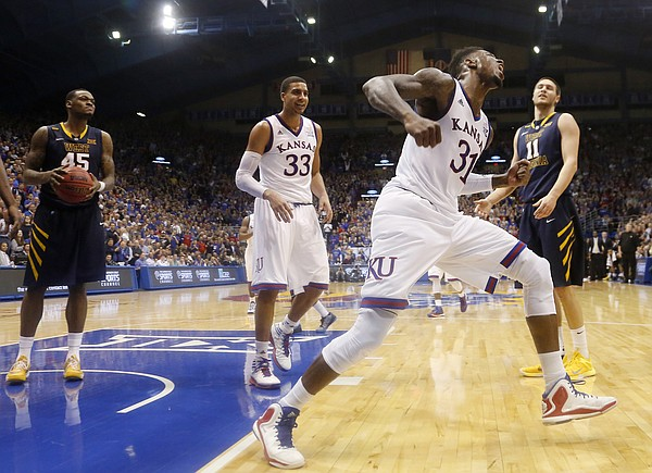Kansas forward Jamari Traylor, right, celebrates a late basket in overtime against the West Virginia Mountaineers Tuesday, March 4, 2015 at Allen Fieldhouse.