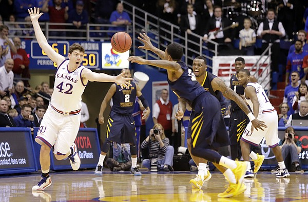 Kansas center Hunter Mickelson (42) knocks the ball loose to create a steal against the West Virginia Mountaineers Tuesday, March 4, 2015 at Allen Fieldhouse.