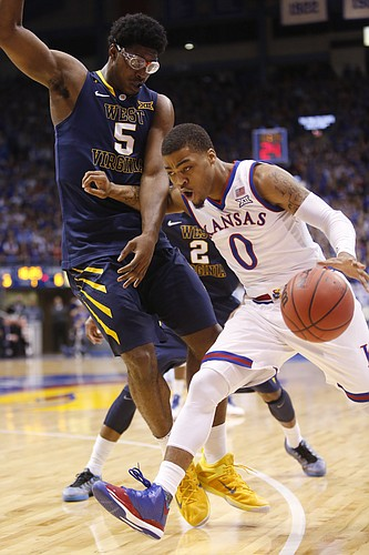 Kansas guard Frank Mason III (0) drives around West Virginia forward Devin Williams (5) during the Jayhawks game against the West Virginia Mountaineers Tuesday, March 4, 2015 at Allen Fieldhouse.