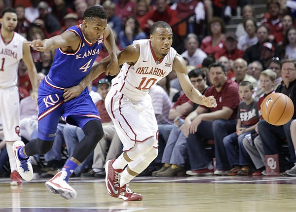 Kansas guard Devonte' Graham (4) and Oklahoma guard Jordan Woodard (10) race to a loose ball in the Jayhawks 75-73 loss to the Oklahoma Sooners Saturday in Norman.