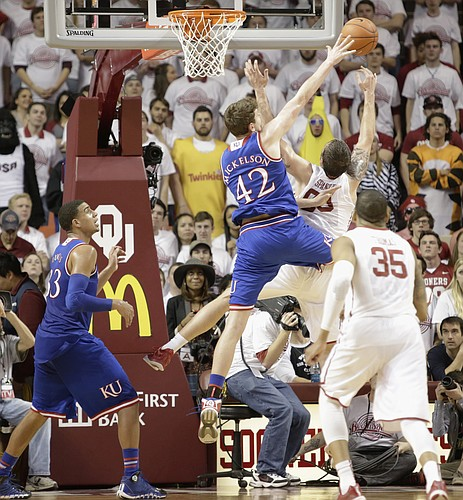 Kansas center Hunter Mickelson (42) blocks a shot  attempt by Oklahoma forward Ryan Spangler during the Jayhawks game Saturday, March 7, 2015 against the Oklahoma Sooners in Norman.