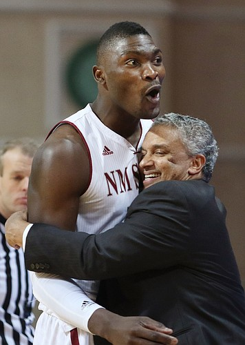 New Mexico State coach Marvin Menzies, right, hugs center Tshilidzi Nephawe toward the end of the second half of the Aggies' victory over Cal State-Bakersfield in the semifinals of the Western Athletic Conference tournament on Friday in Las Vegas. Nephawe is one of four seniors Menzies will count on when the Aggies open the NCAA Tournament against Kansas on Friday in Omaha, Nebraska.