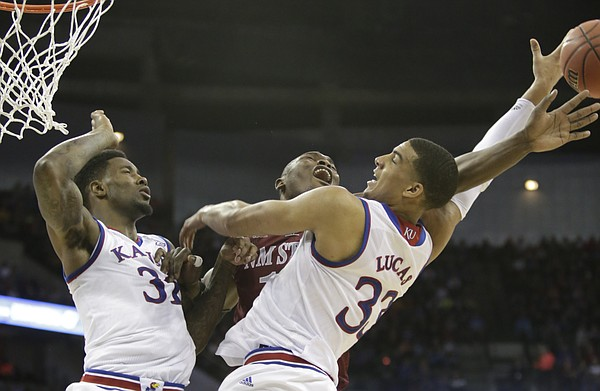 Kansas forward Jamari Traylor (31), left, and Landen Lucas (33) right, go for a rebound against New Mexico State center Tshilidzi Nephawe (15) in the Jayhawks second-round NCAA tournament game against New Mexico State Friday, March 20, 2015 at the CenturyLink Center, Omaha, Neb.