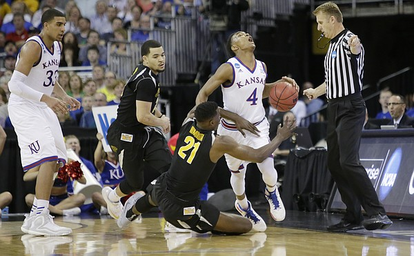 Kansas guard Devonté Graham (4) is fouled after getting a steal on Wichita State center Tom Wamukota (21) in the Jayhawks' third-round NCAA Tournament game against Wichita State Sunday, March 22, 2015 at the CenturyLink Center, Omaha, Neb.