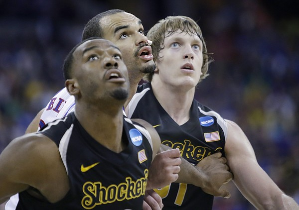 Kansas forward Perry Ellis (34) positions himself for a rebound against  Wichita State center Tom Wamukota, left and Ron Baker, left, in the first-half of the Jayhawks' third-round NCAA Tournament game against Wichita State Sunday, March 22, 2015.