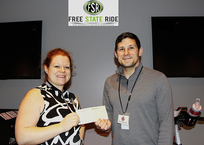 Elliot Johnson, Development Coordinator for Health Care Access, received the donation from Erin Hayden, Free State Ride Instructor, at Body Boutique.