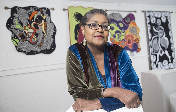 "Quilter and historian Marla Jackson is pictured in front of her quilts on display at the Percolator, 913 Rhode Island St., as part of Jackson's upcoming exhibition, ""Tell Mama."" The exhibit, which opens during this month's Final Friday, features 10 quilts that honor her mother, Fern Hill."