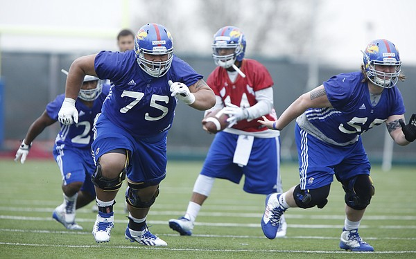 Kansas offensive lineman Junior Visinia (75) and Jacob Bragg (55) take off as the ball is snapped to quarterback Michael Cummings during spring practice on Tuesday, March 24, 2015.