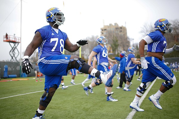 Kansas offensive lineman Larry Mazyck warms up with his teammates during spring practice on Tuesday, March 24, 2015.