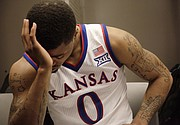 Frank Mason III, sits by his locker after the Jayhawks' 78-65 loss to Wichita State Sunday, March 22, 2015. The narrow framing creates impact and a clean image but doesn't provide readers a larger context.
