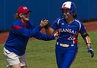 Chanin Naudin gets a high five from Kansas coach Megan Smith as she rounds third base after hitting a second inning solo home run during a game against Texas at Arrocha Ballpark on March 29, 2015.