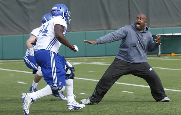 Kansas University defensive line coach Calvin Thibodeaux gets into a drill during a spring practice on Thursday March 26, 2015.