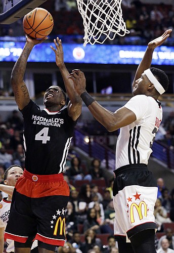 East forward Dwayne Bacon, left, of Oak Hill Academy, Mouth of Wilson, Va., shoots against West forward Carlton Bragg of Villa Angela-St. Joseph of Cleveland, during the second half of the McDonald's All-American boys basketball game in Chicago on Wednesday, April 1, 2015. The East won 111-91. (AP Photo/Nam Y. Huh)
