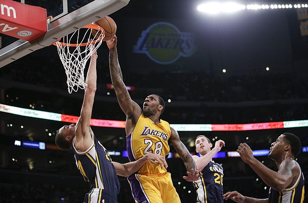 Los Angeles Lakers' Tarik Black, center, goes up for a basket during the second half of an NBA basketball game against the Utah Jazz, Thursday, March 19, 2015, in Los Angeles. The Jazz 80-73. (AP Photo/Jae C. Hong)