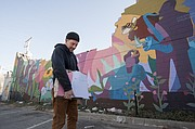 Lawrence artist Dave Loewenstein holds a piece of his Pollinators mural after construction workers began to dismantle the artwork at 9th and New Hampshire on Friday, March 6, 2015.