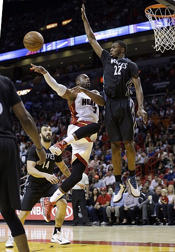 Miami Heat guard Dwyane Wade (3) passes against Minnesota Timberwolves guard Andrew Wiggins (22) in the second half of an NBA basketball game, in Miami, Saturday, Nov. 8, 2014. The Heat won 102-92. (AP Photo/Alan Diaz)