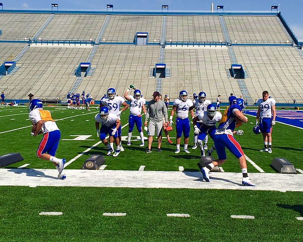 CCR fan and KU linebackers coach Kevin Kane keeps an eye on a group of Jayhawks working through a tackling drill during Tuesday's practice.