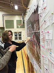 Susan Tate, CEO of the Lawrence Arts Center, pins up a note on a map of Ninth Street at Thursday night's public art workshop.