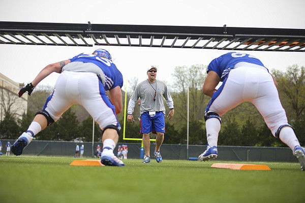 Kansas run game coordinator and offensive line coach Zach Yenser works with the line during practice on Tuesday, April 14, 2015