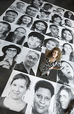 Lawrence photographer and artist Rachael Perry stands among a handful of the 650 portraits of local residents she photographed for the Lawrence Inside Out community photo project. Perry set out take black-and-white portraits of anyone who considered themselves part of the arts community.
