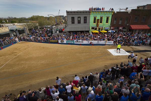 Competitor Christian Cantwell throws up his arms as he watches his final throw of the night along with hundreds of spectators during the Downtown Olympic Shot Put event on Friday, April 17, 2015 at the intersection of Eighth and New Hampshire streets. Cantwell's won the competition with a throw of 70 feet six and a half inches.