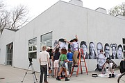 Youths at Van Go Mobile Arts, 715 New Jersey St., install photos for Lawrence Inside Out project on the exterior of the building during a workshop Friday.
