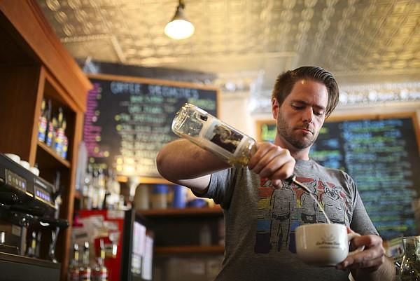 Rob Schulte, a barista at La Prima Tazza, prepares a drink on Tuesday, April 21, 2015.