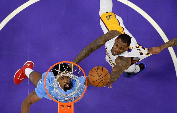 Los Angeles Clippers center DeAndre Jordan, left, and Los Angeles Lakers forward Tarik Black battle for a rebound as Clippers forward Matt Barnes grabs Blacks jersey during the first half of an NBA basketball game, Sunday, April 5, 2015, in Los Angeles. (AP Photo/Mark J. Terrill)