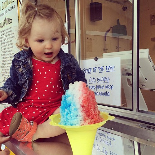 In this 2014 photo, Kensington Bartel enjoys a shaved-ice treat from SnoFlower. Her parents, Kyle and Lori Bartel, own the Lawrence-based truck.