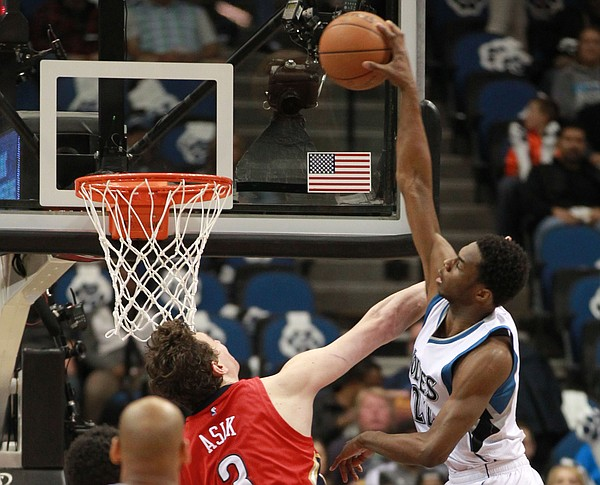 Minnesota Timberwolves Andrew Wiggins (22) dunks on New Orleans Pelicans Omer Asik in the half of an NBA basketball game Monday, April 13, 2015, in Minneapolis. (AP Photo/Andy Clayton-King)