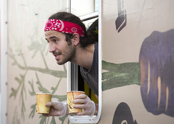 Quent Cole peeks out of the Purple Carrot food truck during the second annual Lawrence Food Truck Festival Saturday evening in east Lawrence.