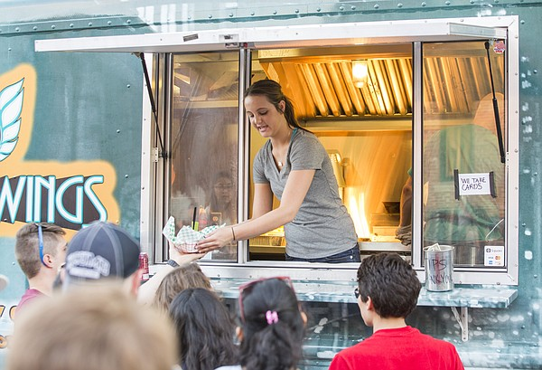 Alex Frank, of Kansas City, Mo., serves a line of customers from the window of the Street Wings food truck during the second annual Lawrence Food Truck Festival, Saturday, May 2, 2015 in east Lawrence.